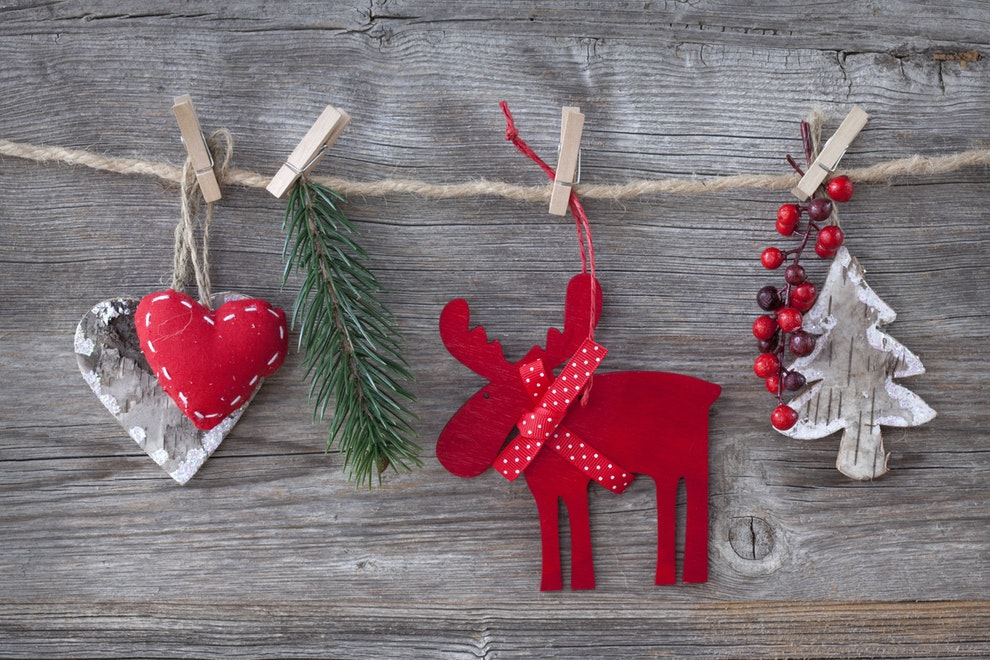 Christmas decorations on a string, a red reindeer, two hearts, berries and and Christmas tree