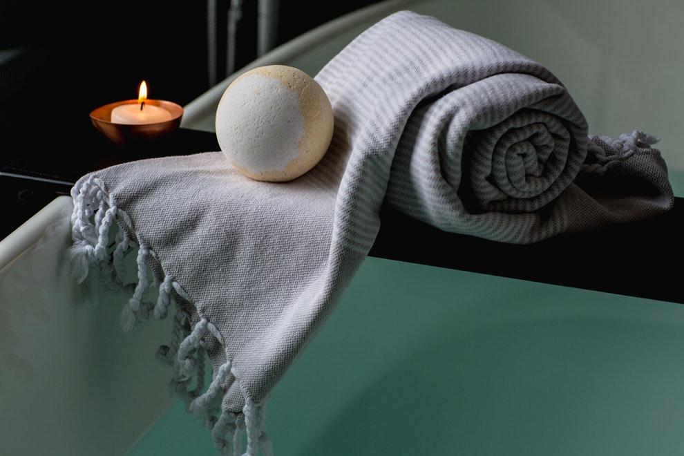 Towel, bath bomb and candle next ot a bathtub